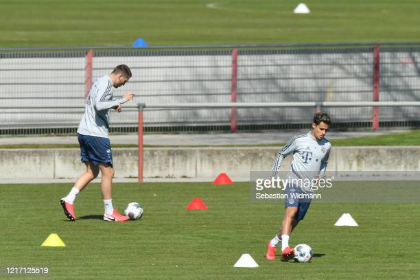 Niklas Suele and Philippe Coutinho of Bayern Muenchen run with the ball during a training session at Saebener Strasse training ground on April 06...