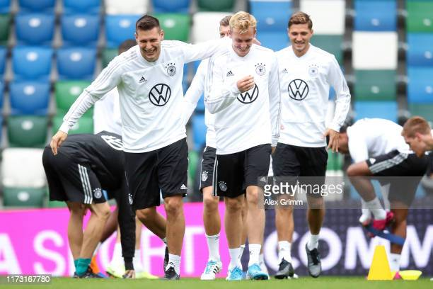 Niklas Suele hugs Julian Brandt during a Germany training session ahead of the UEFA Euro 2020 qualifier match between Northern Ireland and Germany at...
