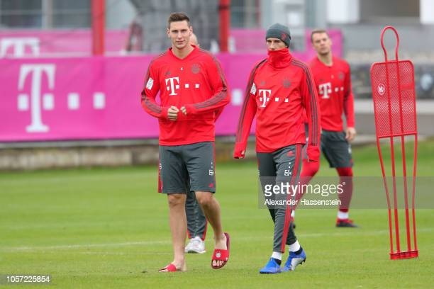 Niklas Suele of Bayern Muenchen arrives with Leon Goretzka for a Bayern Muenchen training session at Saebener Strasse training ground on November 4...