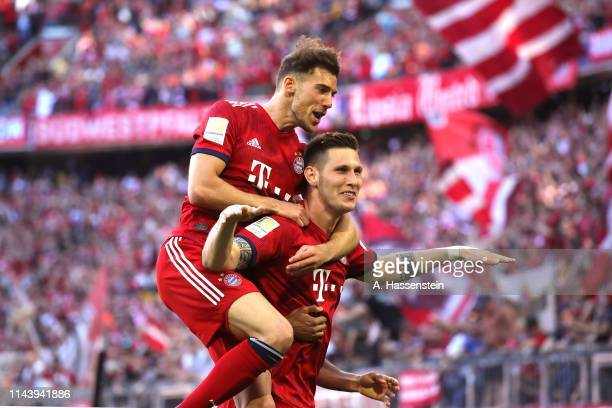 Niklas Suele of Bayern Muenchen celebrates scoring the opening goal with his team mate Leon Goretzka during the Bundesliga match between FC Bayern...