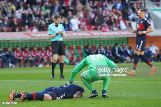 Niklas Suele of Bayern Muenchen lies on the pitch after scoring an own goal to make it 10 while goalkeeper Sven Ulreich of Bayern Muenchen checks on...