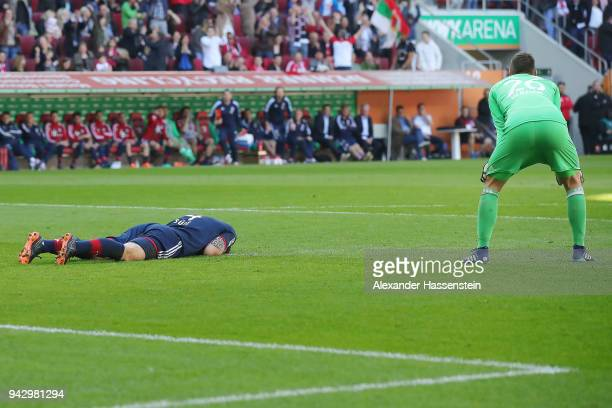 Niklas Suele of Bayern Muenchen lies on the pitch after scoring an own goal to make it 10 while goalkeeper Sven Ulreich of Bayern Muenchen looks on...