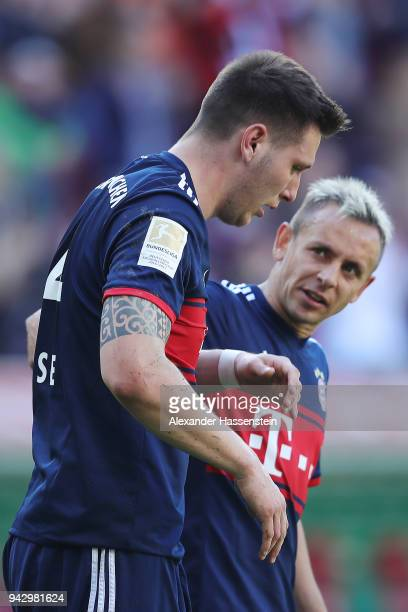 Niklas Suele of Bayern Muenchen looks dejected after scoring an own goal to make it 10 while Rafinha of Bayern Muenchen checks on him during the...