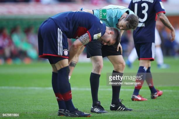Niklas Suele of Bayern Muenchen looks dejected after scoring an own goal to make it 10 referee Markus Schmidt checks on him during the Bundesliga...