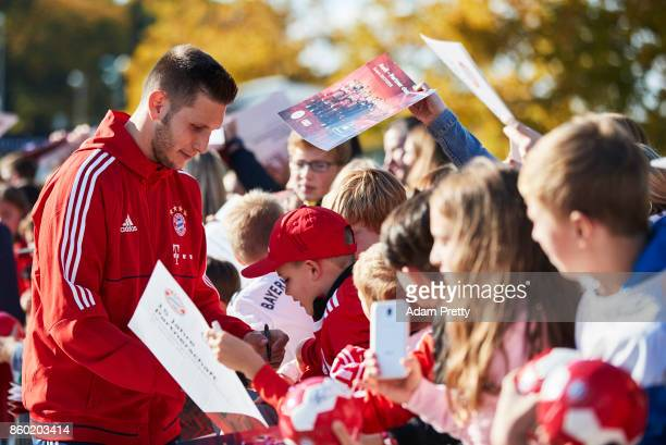 Niklas Suele of Bayern Muenchen signs autographs for fans during the FC Bayern Muenchen New Car Handover at the Audi Forum on October 11 2017 in...