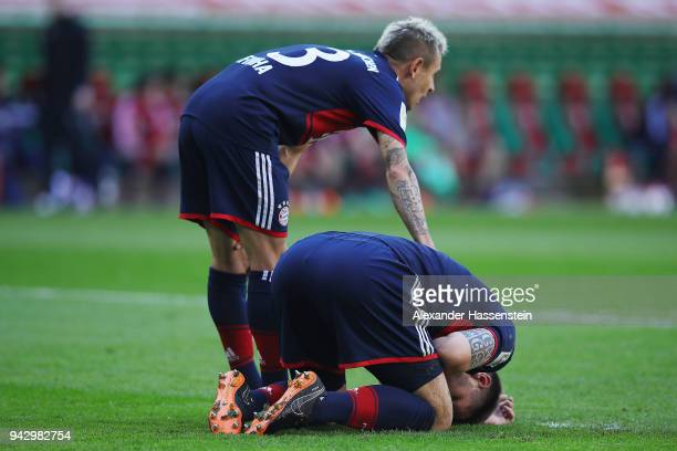 Niklas Suele of Bayern Muenchen sits on the pitch after scoring an own goal to make it 10 while Rafinha of Bayern Muenchen checks on him during the...