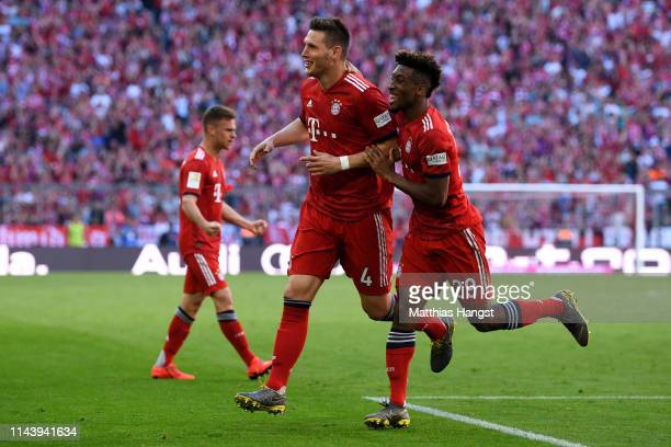Niklas Suele of Bayern Munich celebrates with team mate Kingsley Coman of Bayern Munich after scoring their team's first goal during the Bundesliga...