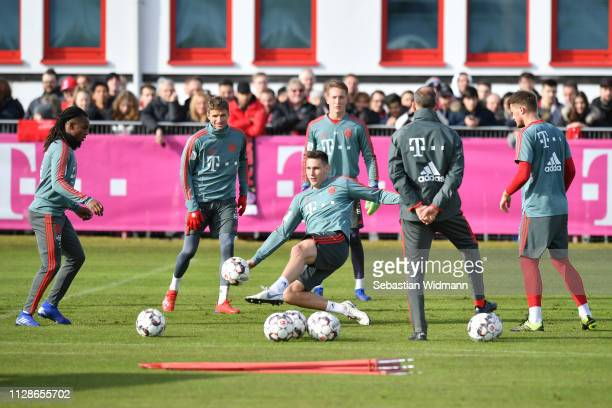 Niklas Suele of Bayern Munich shoots the ball while Renato Sanches and Thomas Mueller watch during a FC Bayern Muenchen training session at Saebener...