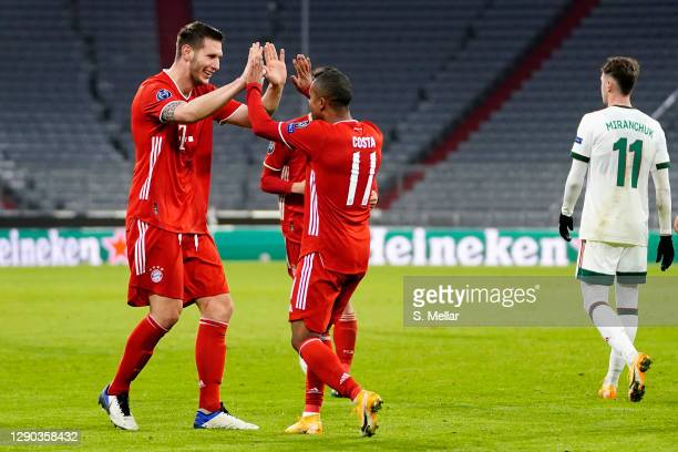 Niklas Suele of FC Bayern Muenchen celebrates with teammate Douglas Costa after scoring his team's first goal during the UEFA Champions League Group...