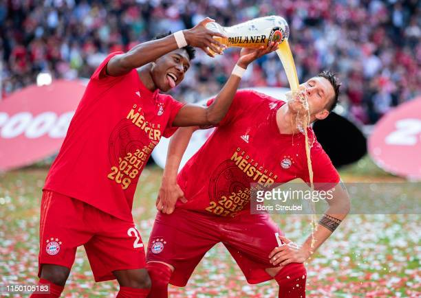 Niklas Suele of FC Bayern Muenchen gets a beer shower from David Alaba of FC Bayern Muenchen to celebrate the championship following the Bundesliga...