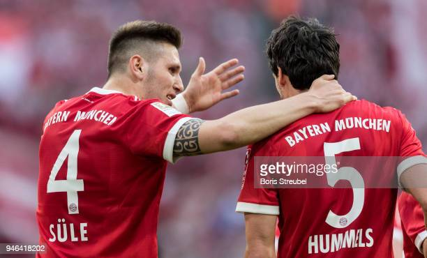 Niklas Suele of FC Bayern Muenchen reacts with Mats Hummels of FC Bayern Muenchen during the Bundesliga match between FC Bayern Muenchen and Borussia...