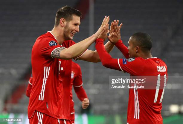 Niklas Suele of FC Bayern Munich celebrates with team mate Douglas Costa after scoring their sides first goal during the UEFA Champions League Group...