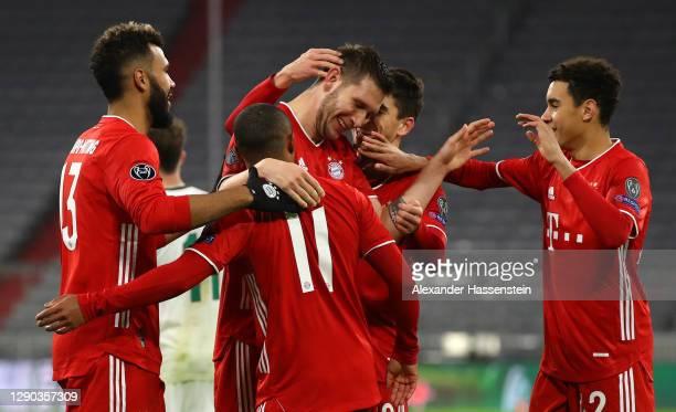 Niklas Suele of FC Bayern Munich celebrates with team mates Douglas Costa, Eric Maxim Choupo-Moting, Marc Roca and Jamal Musiala after scoring their...