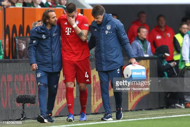 Niklas Suele of FC Bayern Munich receives medical treatment during the Bundesliga match between FC Augsburg and FC Bayern Muenchen at WWKArena on...