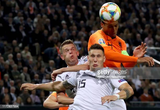 Niklas Suele of Germany and his team mate Matthias Ginter battle for the ball with Virgil Van Dijk of Netherlands during the UEFA Euro 2020 qualifier...