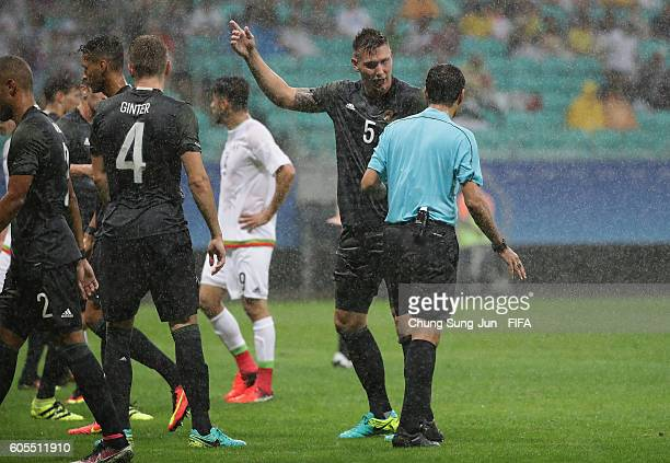 Niklas Suele of Germany argue with referee Alireza Faghani during the Men's first round match between Mexico v Germany at Arena Fonte Nova on August...
