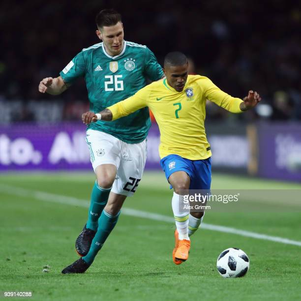 Niklas Suele of Germany is challenged by Douglas Costa of Brazil during the international friendly match between Germany and Brazil at Olympiastadion...