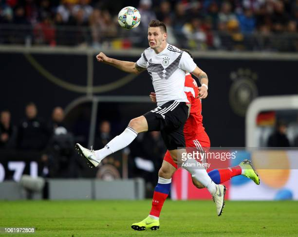 Niklas Suele of Germany wins a header over Anton Zabolotny of Russia during the International Friendly match between Germany and Russia at Red Bull...