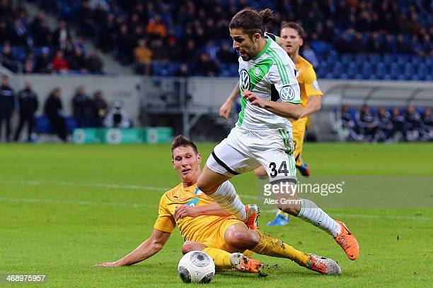Niklas Suele of Hoffenheim tackles Ricardo Rodriguez of Wolfsburg for the second penalty during the DFB Cup quarterfinal match between 1899...