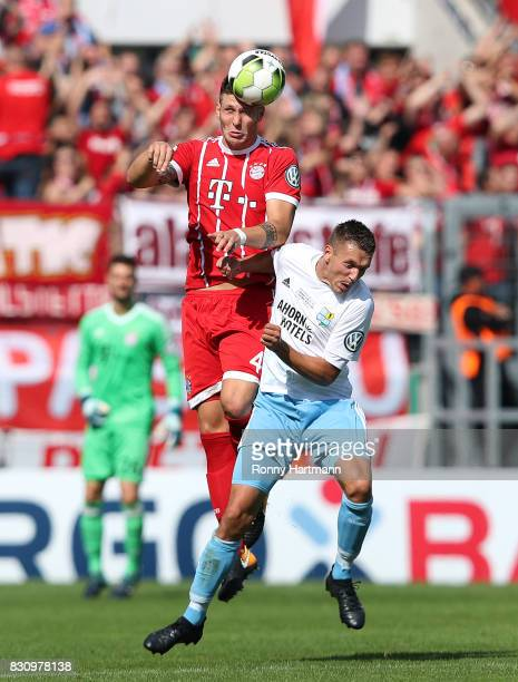 Niklas Suele of Muenchen and Daniel Frahn of Cottbus head for the ball during the DFB Cup first round match between Chemnitzer FC and FC Bayern...