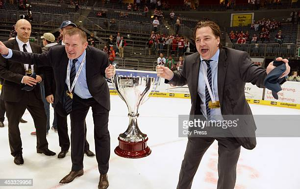 Niklas Sundblad and Petri Liimatainen hold the trophy after game seven of the DEL playoff final on April 29, 2014 in Cologne, Germany.