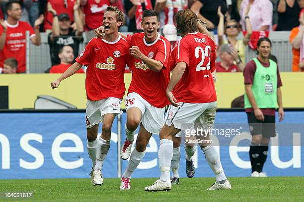 Niko Bungert of Mainz celebrates his team's first goal with team mates Adam Szalai and Christian Fuchs during the Bundesliga match between FSV Mainz...