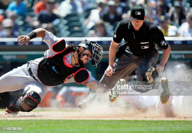 Niko Goodrum of the Detroit Tigers beats the tag from catcher Jorge Alfaro of the Miami Marlins to score on a sacrifice fly hit by Ronny Rodriguez...
