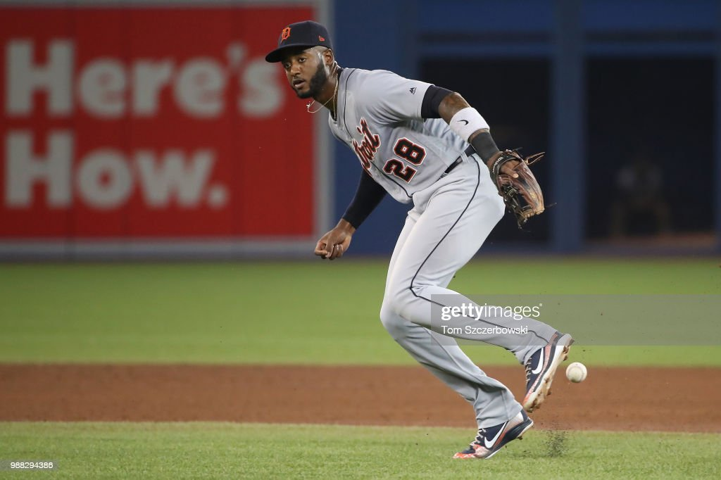 Niko Goodrum #28 of the Detroit Tigers cannot come up with an infield single hit by Devon Travis #29 of the Toronto Blue Jays in the eighth inning during MLB game action at Rogers Centre on June 30, 2018 in Toronto, Canada.