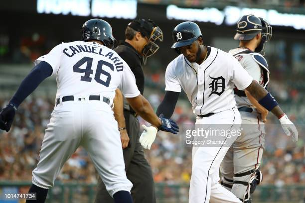 Niko Goodrum of the Detroit Tigers celebrates his two run home run in the fourth inning with Jeimer Candelario in front of Mitch Garver of the...