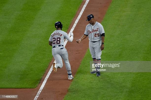 Niko Goodrum of the Detroit Tigers celebrates with third base coach Dave Clark after hitting a home run in the fifth inning against the Baltimore...