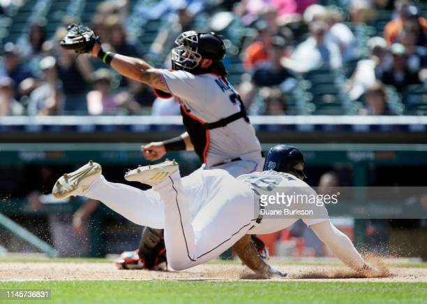 Niko Goodrum of the Detroit Tigers dives at home plate to score against catcher Jorge Alfaro of the Miami Marlins on a sacrifice fly hit by Ronny...