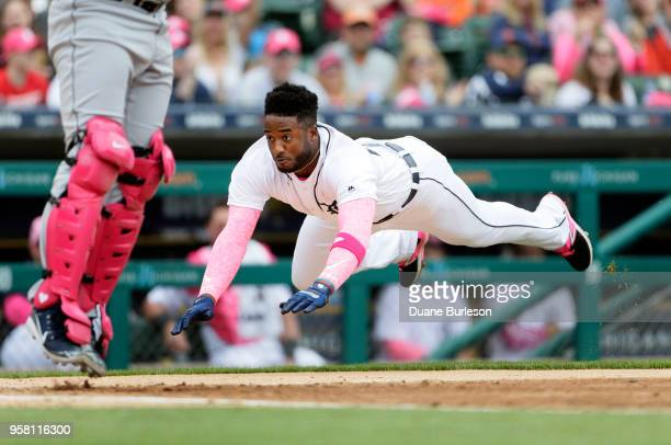 Niko Goodrum of the Detroit Tigers dives into home plate to score against the Seattle Mariners from second base on a single by Mikie Mahtook during...