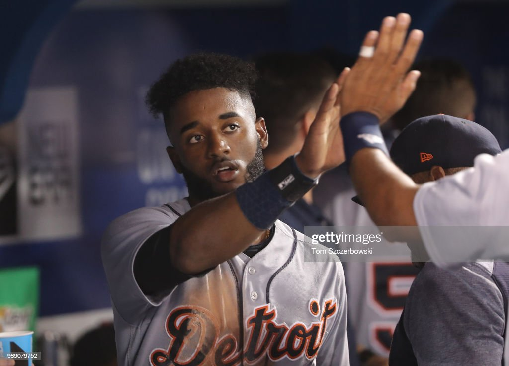 Niko Goodrum #28 of the Detroit Tigers is congratulated by teammates in the dugout after scoring a run in the sixth inning during MLB game action against the Toronto Blue Jays at Rogers Centre on July 1, 2018 in Toronto, Canada.