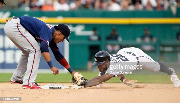 Niko Goodrum of the Detroit Tigers keeps his fingers on second base after making the steal as shortstop Jorge Polanco of the Minnesota Twins...