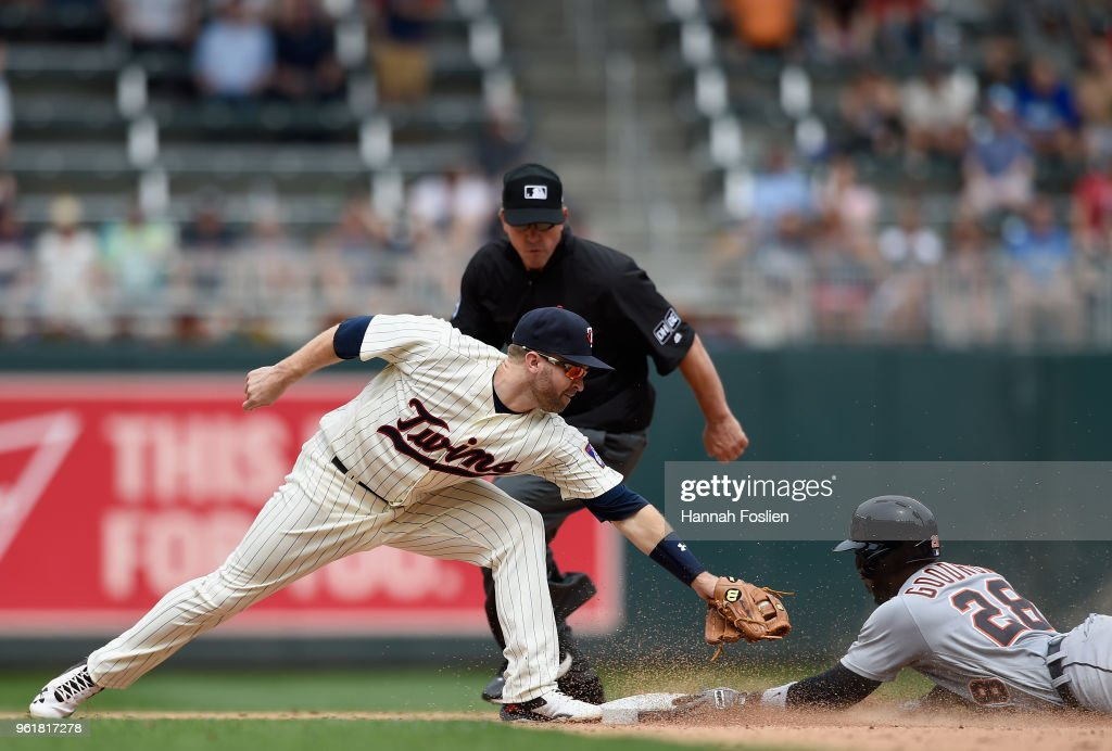 Niko Goodrum #28 of the Detroit Tigers slides into second base safely with a double as Brian Dozier #2 of the Minnesota Twins applies the tag and umpire Jeff Kellogg #8 looks on during the ninth inning of the game on May 23, 2018 at Target Field in Minneapolis, Minnesota. The Tigers defeated the Twins 4-1.