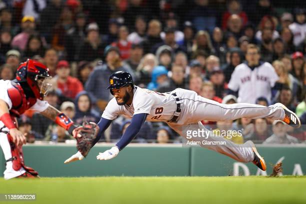 Niko Goodrum of the Detroit Tigers slides safely into home under the tag of Christian Vazquez of the Boston Red Sox in the fourth inning during the...