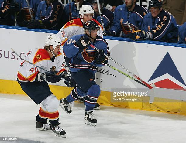 Niko Kapanen of the Atlanta Thrashers battles for position against Greg Jacina and Ari Vallin of the Florida Panthers during an exhibition game on...