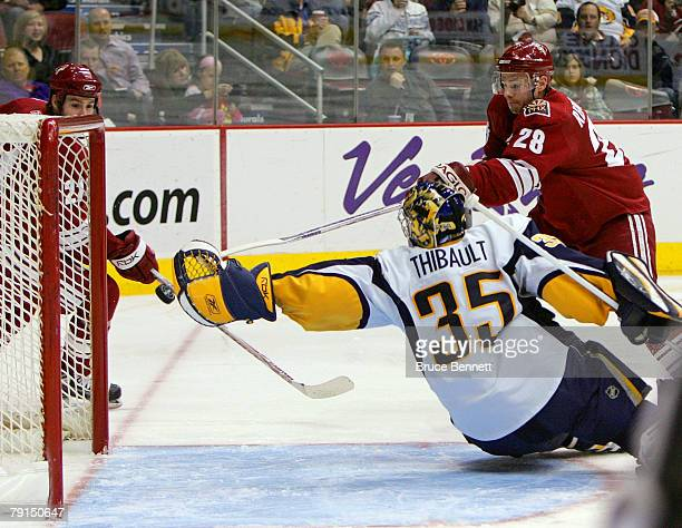 Niko Kapanen of the Phoenix Coyotes scores a second period goal against Jocelyn Thibault of the Buffalo Sabres as Steven Reinprecht moves into the...