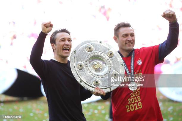 Niko Kovac head coach of Bayern Munich lifts the trophy with his brother and assistent coach Robert Kovac following the Bundesliga match between FC...