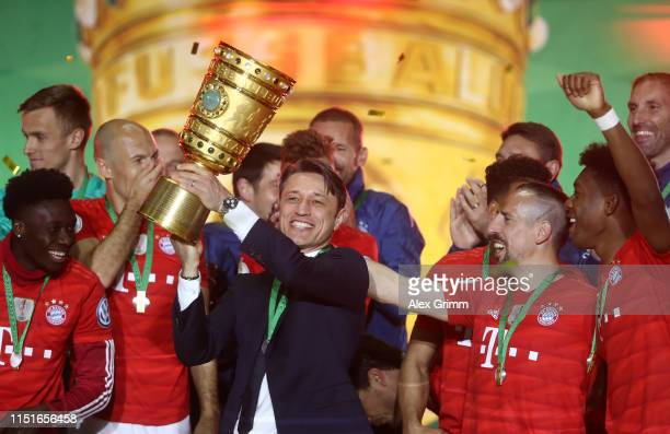 Niko Kovac Manager of Bayern Munich lifts the trophy in celebration with team mates after the DFB Cup final between RB Leipzig and Bayern Muenchen at...
