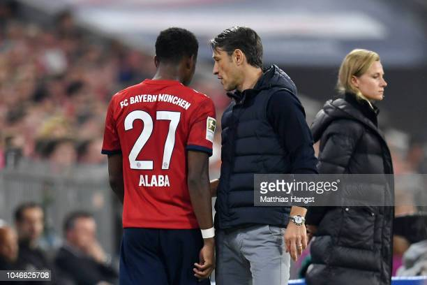 Niko Kovac Manager of Bayern Munich speaks with David Alaba of Bayern Munich as he comes of injured during the Bundesliga match between FC Bayern...