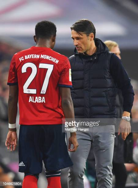 Niko Kovac Manager of Bayern Munich speaks with David Alaba of Bayern Munich as he is substituted during the Bundesliga match between FC Bayern...
