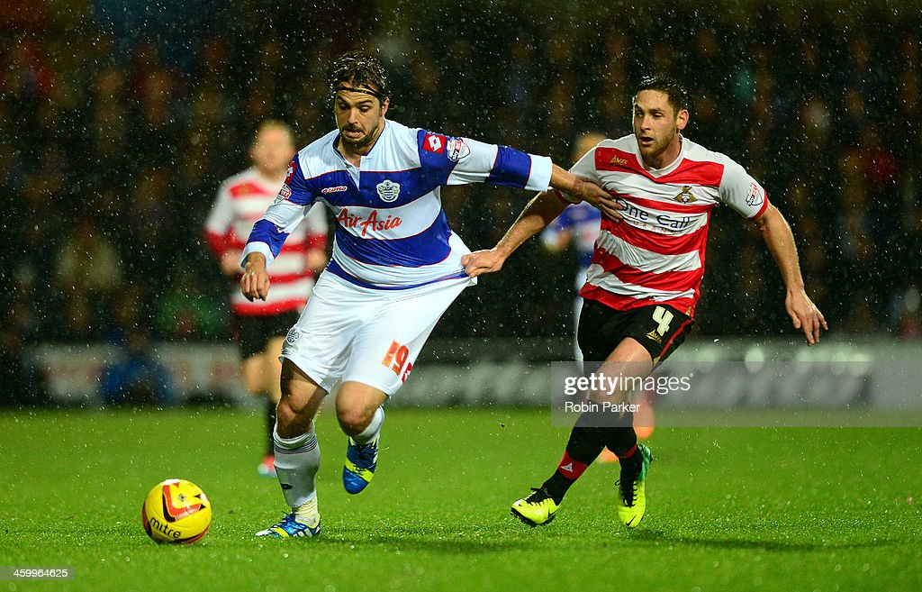 Niko Kranjcar of Queens Park Rangers is challenged by Dean Furman of Doncaster Rovers during the Sky Bet Championship match between Queens Park Rangers and Doncaster Rovers at Loftus Road on January 1, 2014 in London, England,
