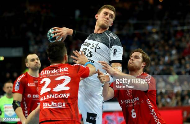 Nikola Bilyk of Kiel challenge Michael Allendorf#22 and Johannes Goll of Melsungen for the ball during the DKB HBL Bundesliga match between THW Kiel...