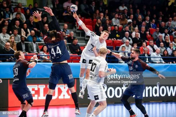 Nikola Bilyk of THW Kiel is shooting the ball against Luka Karabatic and Nikola Karabatic of Paris Saint Germain during the Champions League match...