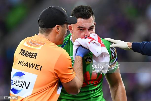 Nikola Cotric of the Raiders is attended to by a team trainer after being kicked in the face during the NRL Qualifying Final match between the...