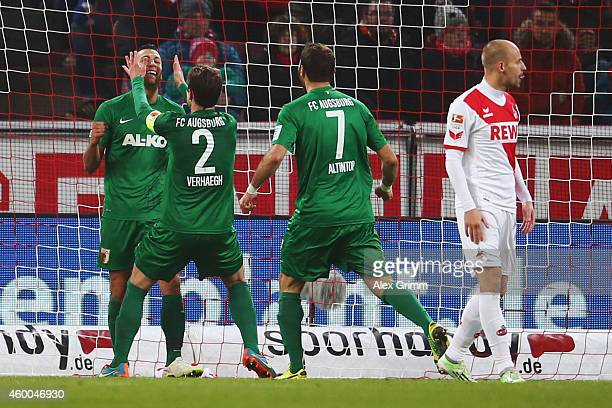 Nikola Durdic of Augsburg celebrates his team's first goal with team mates Paul Verhaegh and Halil Altintop as Miso Brecko of Koeln reacts during the...