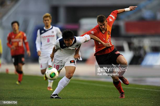 Nikola Jakimovski of Nagoya Grampus and Tomonobu Yokoyama of Cerezo Osaka compete for the ball during the JLeague Yamazaki Nabisco Cup match between...