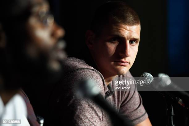 Nikola Jokic listens to his teammate Will Barton during a press conference as the Nuggets to announce new contracts for them at the Pepsi Center on...