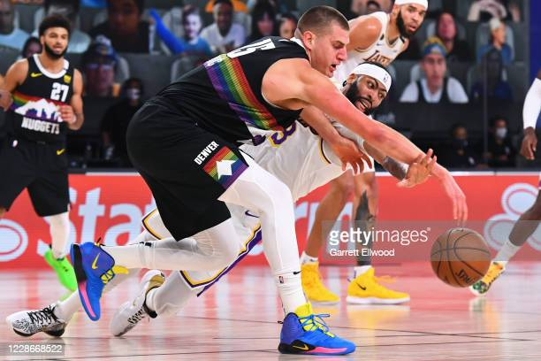 Nikola Jokic of the Denver Nuggets and Anthony Davis of the Los Angeles Lakers dive for the loose ball during Game Three of the Western Conference...